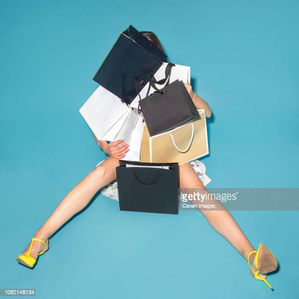 high angle view of woman with shopping bags sitting on blue background - spending money stock pictures, royalty-free photos & images