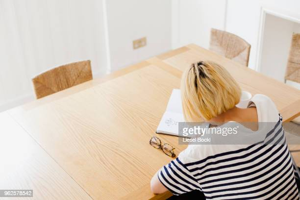 high angle view of woman with short hair writing in diary at table - nur japaner stock-fotos und bilder