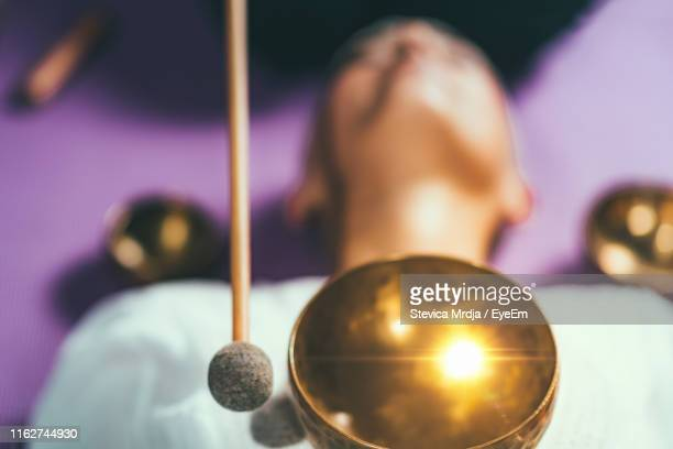 high angle view of woman with singing bowl relaxing while lying in spa - gong stock pictures, royalty-free photos & images