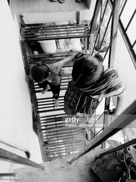 High Angle View Of Woman With Son On Stairs