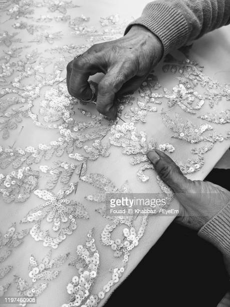high angle view of woman working on fabric - fouad el-khabbaz stock pictures, royalty-free photos & images