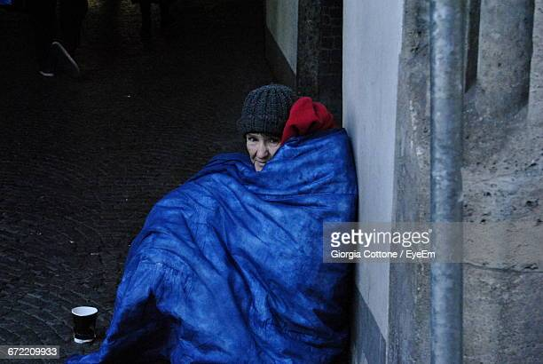 High Angle View Of Woman Wrapped In Blanket Sitting Against Wall