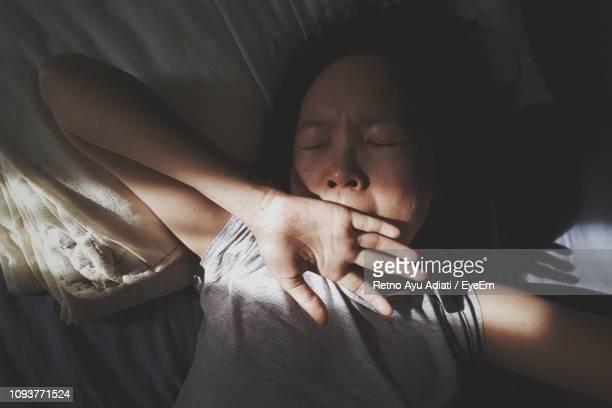 high angle view of woman yawning while lying on bed at home - waking up stock pictures, royalty-free photos & images