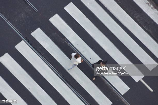 high angle view of women crossing road - zebra crossing stock photos and pictures