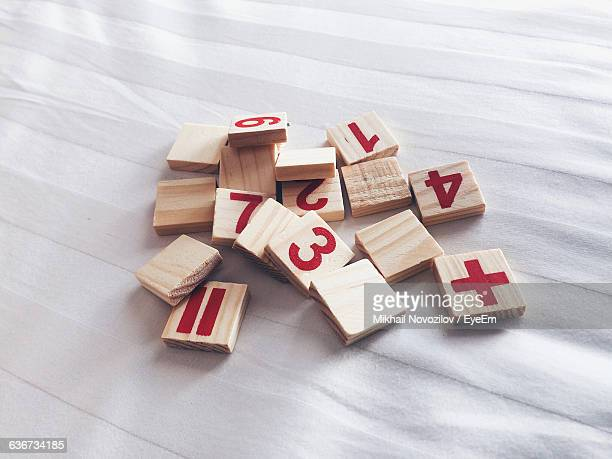 High Angle View Of Wooden Blocks With Numbers And Mathematical Symbols On Fabric