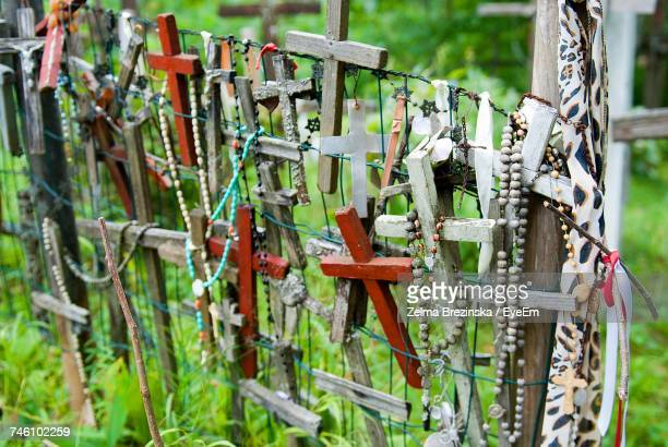 High Angle View Of Wooden Crosses Attached To Fence