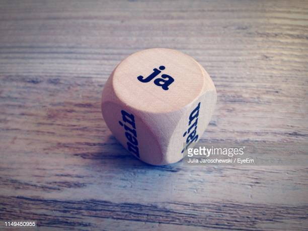high angle view of wooden dice on table - entscheidung stock-fotos und bilder