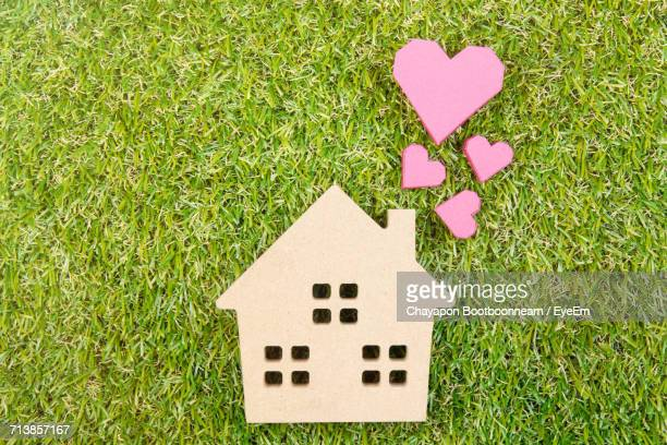 High Angle View Of Wooden House Toy With Heart Shape Paper Boxes On Grassy Field