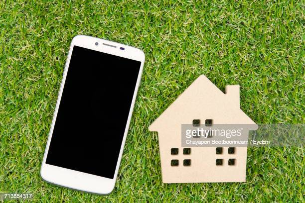 High Angle View Of Wooden House Toy With Mobile Phone On Grassy Field