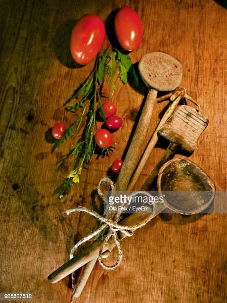 High Angle View Of Wooden Kitchen Utensils By Vegetables On Table