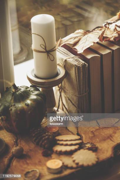 high angle view of wooden table with autumnal ornaments by the window - embellishment stock pictures, royalty-free photos & images