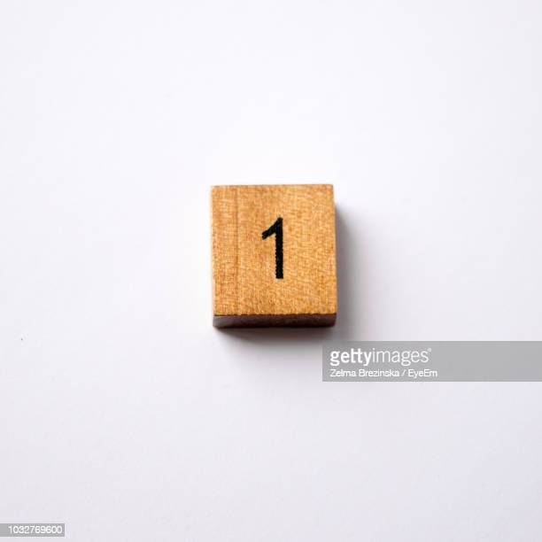 high angle view of wooden toy block on white background - getal stockfoto's en -beelden