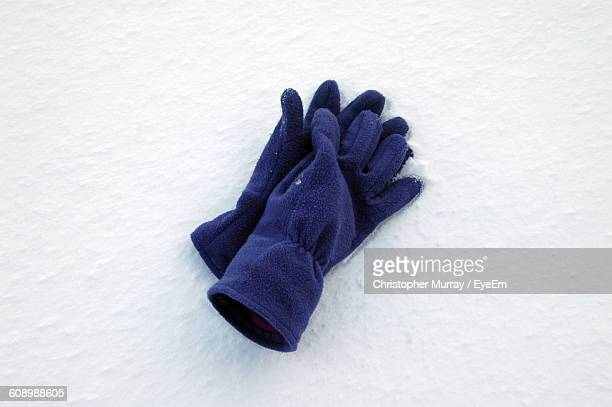 High Angle View Of Woolen Gloves Pair On Snow