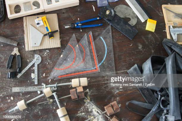 High Angle View Of Work Tools On Wooden Table At Workshop
