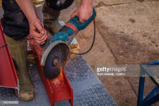 High Angle View Of Worker Cutting Metal With Electric Saw At Workshop