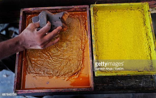High Angle View Of Worker Holding Printing Block Next To Color Container