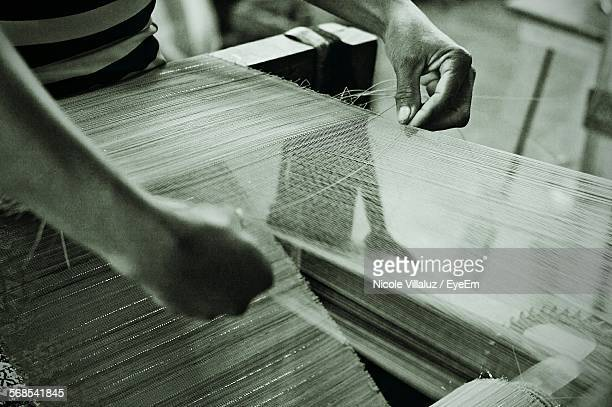 High Angle View Of Worker Weaving Fabric