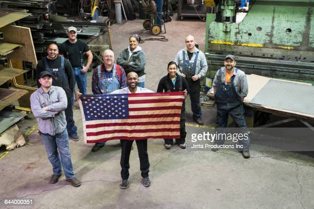 high angle view of workers and businessman holding american flag in factory - カバーオール ストックフォトと画像
