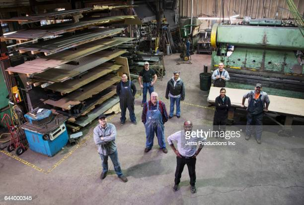 high angle view of workers and businessman standing in factory - カバーオール ストックフォトと画像