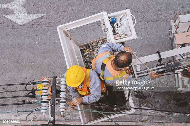 high angle view of workers working at construction site - power line stock pictures, royalty-free photos & images