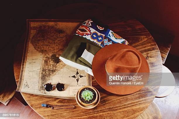 High Angle View Of World Map With Jacket And Hat On Table