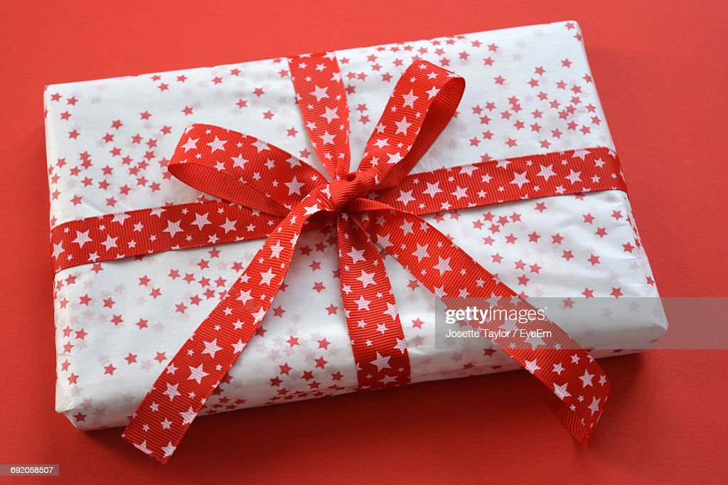 high angle view of wrapped christmas present on red background stock photo
