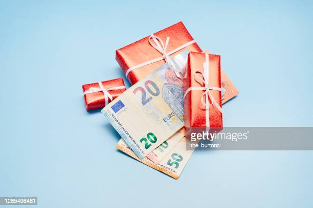 high angle view of wrapped christmas presents and euro banknotes on blue background, christmas bonus - christmas cash stock pictures, royalty-free photos & images