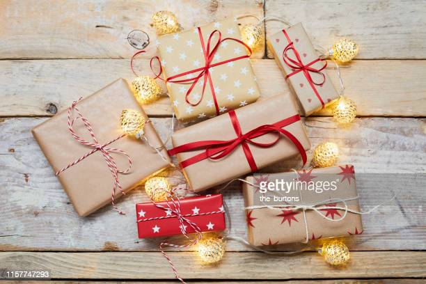 high angle view of wrapped christmas presents and string lights on wooden table - stars and strings 2019 stock photos and pictures