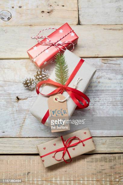 """high angle view of wrapped christmas presents with """"for you"""" label on wooden table - stars and strings 2019 stock photos and pictures"""