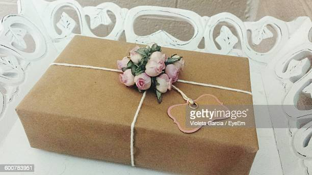 High Angle View Of Wrapped Gift Box With Pink Flowers In Tray