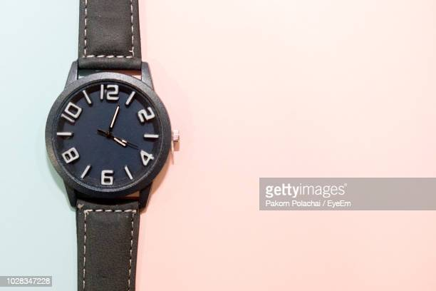 high angle view of wristwatch over colored background - wrist watch stock pictures, royalty-free photos & images