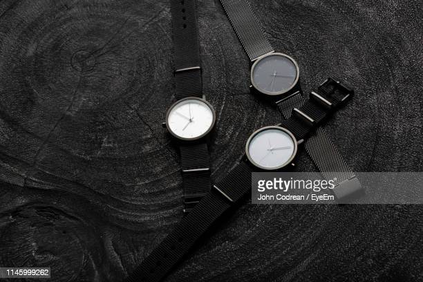 high angle view of wristwatches on black table - wristwatch stock pictures, royalty-free photos & images