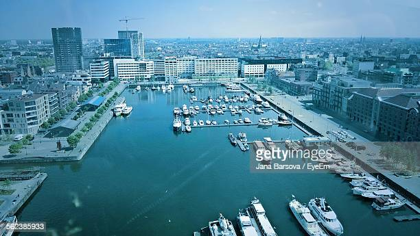 high angle view of yachts moored on river in city - antwerpen stad stockfoto's en -beelden