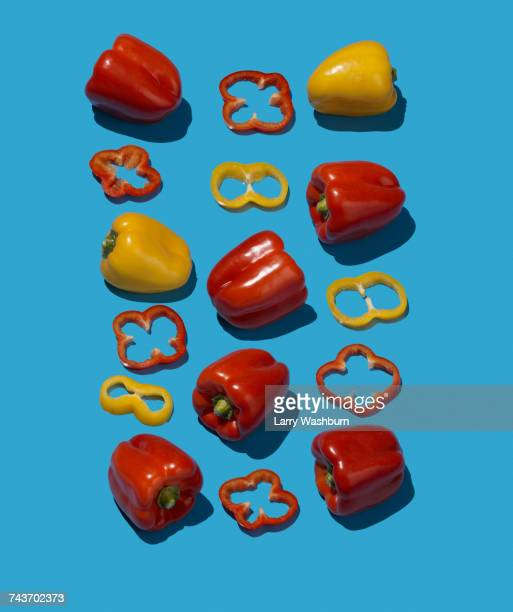 High angle view of yellow and red bell peppers on blue background