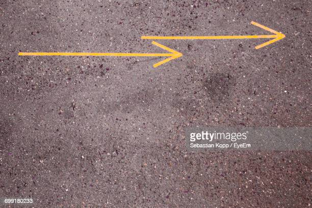 High Angle View Of Yellow Arrow Signs On Street