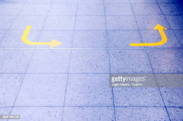 High Angle View Of Yellow Arrow Symbol On Footpath