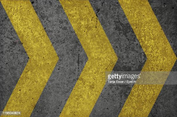 high angle view of yellow arrow symbol on road - dividing line road marking stock pictures, royalty-free photos & images