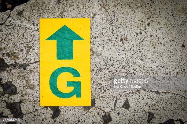 high angle view of yellow arrow symbol on road - letra g - fotografias e filmes do acervo