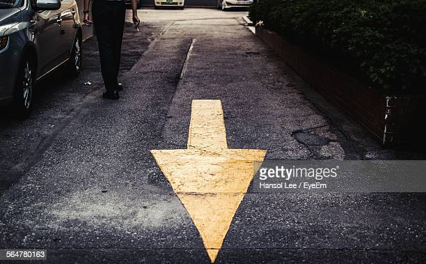 High Angle View Of Yellow Arrow Symbol On Street