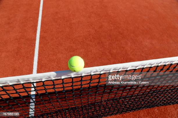High Angle View Of Yellow Ball On Net At Tennis Court