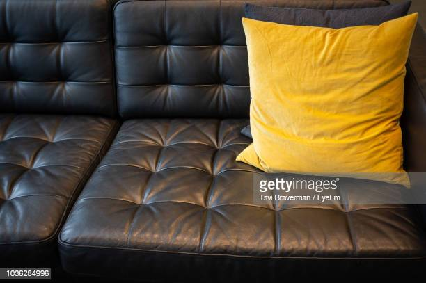 high angle view of yellow cushion on sofa at home - cushion stock photos and pictures