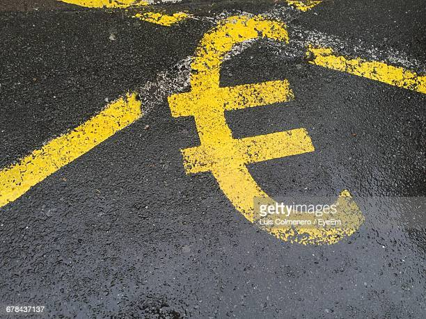 High Angle View Of Yellow Euro Symbol On Wet Road