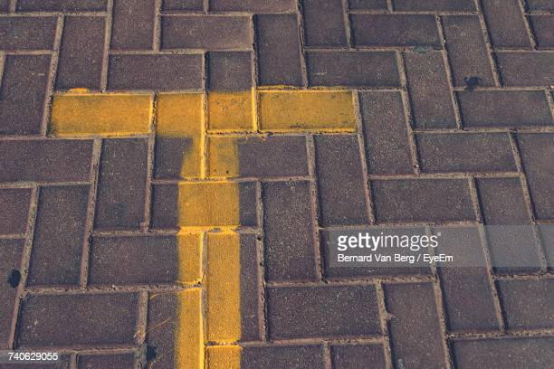 High Angle View Of Yellow Letter T On Footpath