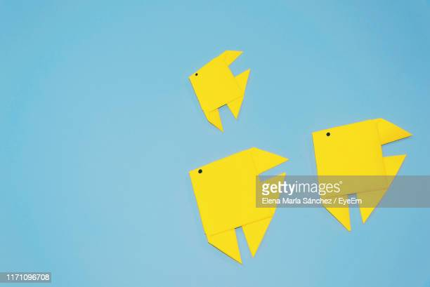 high angle view of yellow paper fish on blue background - origami foto e immagini stock