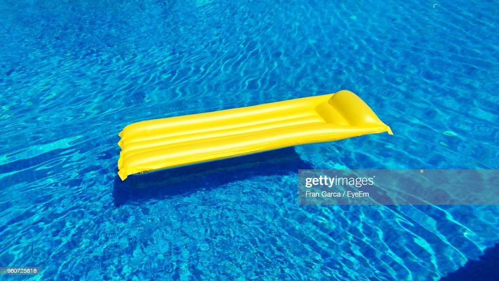 High Angle View Of Yellow Pool Raft Floating On Swimming Pool : Stock Photo
