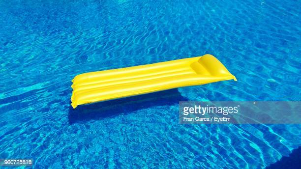 High Angle View Of Yellow Pool Raft Floating On Swimming Pool