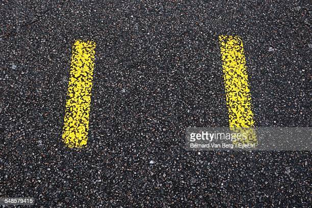 High Angle View Of Yellow Road Markings On Street