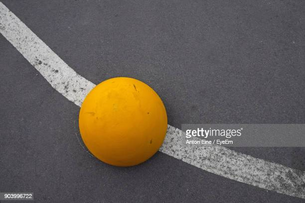 high angle view of yellow spherical bollard on street - bollard stock photos and pictures