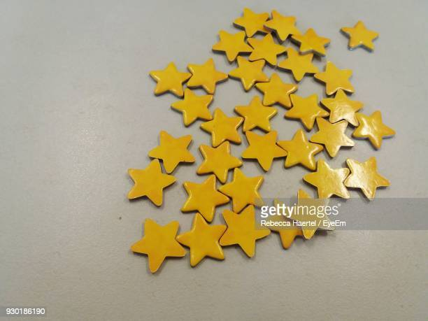 high angle view of yellow star shaped decoration on table - rebecca haertel stock-fotos und bilder