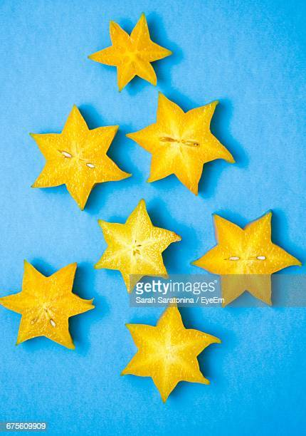 High Angle View Of Yellow Starfruit Slices On Blue Background